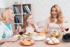 Mom, grandmother and little girl are dining together at home. stock photography
