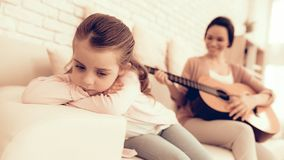 Mom with Guitar in Hand and Sad Girl Lie on Sofa. Sad Girl Lie on Sofa. Kids Games. Rest at Home. Child Development. Mom and Daughter Play. Happy Mom and Child royalty free stock photo