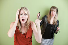 Mom with Hand on Head. Annoyed mom with daughter listening on headphones Stock Photography