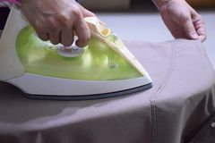 Mom hands holding Electric steam iron. Steaming clothes,shallow depth of field royalty free stock photos