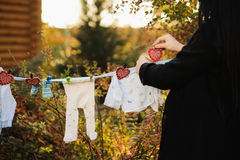 Mom hanging baby clothes on a clothesline outdoor in sunny autum Stock Images