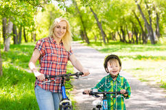 Mom have fun with her son - riding a bicycle in a park Royalty Free Stock Photos