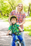 Mom have fun with her son - riding a bicycle in a park Stock Images