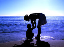 Mom helping boy at the beach. Mom helping her small boy on a beautifull blue beach Royalty Free Stock Photo