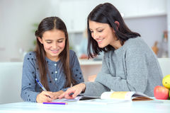 Mom helping daughter do homework Stock Photography