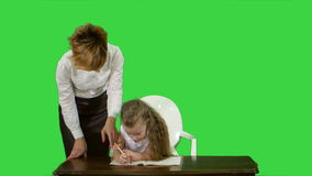 Mom helping daughter with homework on a green screen, chroma key stock footage