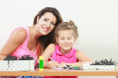 Mom helping daughter with homework Stock Photos