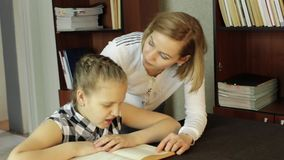 Mom helping her daughter do homework. schoolgirl makes lessons.  stock footage