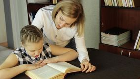 Mom helping her daughter do homework. schoolgirl makes lessons stock video