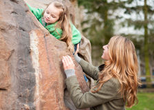 Mom helping her little daughter to climb a rock Stock Images