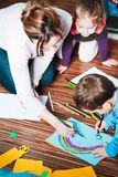 Mom helping her little son drawing a colorful picture of car using pencil crayons. Sitting on floor. Shot from above stock photo