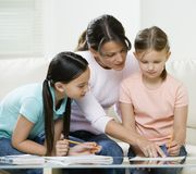 Mom helping kids with homework. Mom helping young kids with homework on coffee table