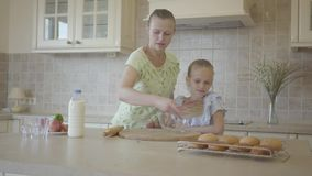 Mother helping and teaching her little cute daughter in modern cozy kitchen to cook cake or pancakes. Happy family. Mom helping and teaching her little cute stock video footage