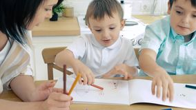 Mom helping two sons to perform drawing markers in the album. Preschool education