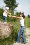 Mom helps daughter to go to the ground Stock Images