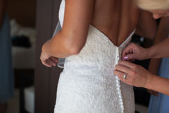 Mom helps dress bride wedding  from a back Stock Photography
