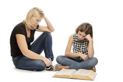 Mom helps her teen daughter to learn lessons, isolated on white background. Quarreled and upset stock image