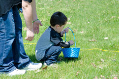Mom helps Little boy in a Easter egg hunt royalty free stock images