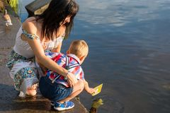 Mom helps the little boy to lower the paper boat to the water. Mom and a her little son launch paper boats in a river in the summer royalty free stock images