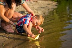 Mom helps the little boy to lower the paper boat to the water. Mom and her son launch paper boats in a river in the summer royalty free stock photography