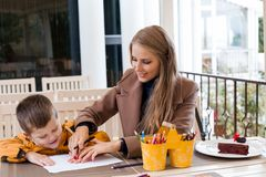 Mom helps son to draw drawing colored pencils. Mother and son draw drawing hands colored pencils Royalty Free Stock Photography