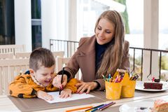 Mom helps son to draw drawing colored pencils. Mother and son draw drawing hands colored pencils Stock Photography