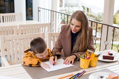 Mom helps son to draw drawing colored pencils. Mother and son draw drawing hands colored pencils Stock Photo