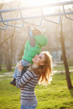 Mom helps son to the horizontal bars. Stock Image