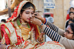 Mom helps young beauty wear traditional jewelry and earrings. JAISALMER, INDIA: Mom helps young beauty wear traditional jewelry and earrings in the nose during royalty free stock photo