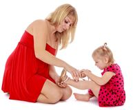 Mom helps young daughter to wear a slipper Royalty Free Stock Image