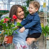 Mom and her baby boy in a plant shop looking at flower. Gardening In Greenhouse. Botanical garden, flower farming stock photos