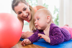 Mom and her baby practicing to crawl in mother and child course Royalty Free Stock Images