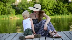 Mom and her blond son hug and chat on the pier by the river. Summer day.  stock footage
