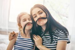 Mom and her daughter are playing. Mom and her child daughter are playing and having fun together. Beautiful funny girl and mother have mustache. Family holidays Royalty Free Stock Photos