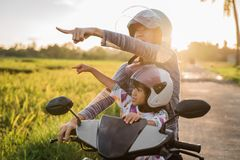 Mom and her child enjoy riding motorcycle scooter stock images