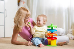 Mom and her child playing with colorful logical Stock Images