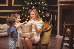 Mom and her children near the Christmas tree stock photography
