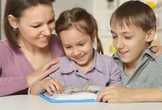 Mom with her children. Reading a book Stock Photos