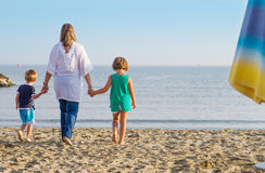Mom and her children walk hand in hand at the beach Stock Photography