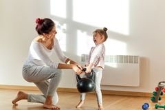 Mom and her daughter with joyful positive emotions go in for sports and raise weights together. royalty free stock image