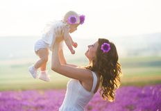 Mom and her daughter in a lavender field. Young mommy and her little daughter in a beautiful wreath are walking in a lavender field. Life in Provence. Brunette Stock Image