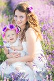 Mom and her daughter in a lavender field. Young mommy and her little daughter in a beautiful wreath are walking in a lavender field. Life in Provence. Brunette Stock Photography