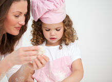 Mom and her daughter making biscuits together Stock Image