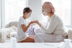 Mom with her daughter making clay face mask stock photos
