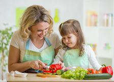 Mom and her daughter preparing vegetables at. Mother and her daughter preparing vegetables at kitchen Royalty Free Stock Photos