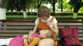 Mom with her daughter, preschool girl lying on the lap of a young woman in the park on the bench. Summer sunny day stock video