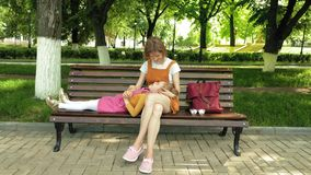 Mom with her daughter, preschool girl lying on the lap of a young woman in the park on the bench. Summer sunny day stock footage