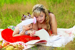 Mom with her daughter reading a book Stock Image