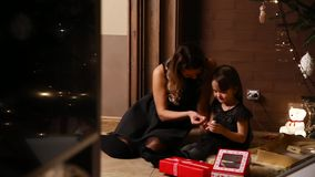 Mom and her daughter sit under a decorated Christmas tree at home consider gifts stock footage