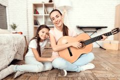 Mom and her daughter are sitting on the floor at home and playing the guitar. They sing to the guitar. royalty free stock photo